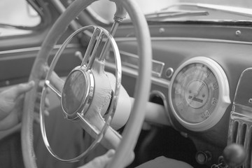 Fototapeta Steering wheel and a dashboard in the interior of an old stylish retro car obraz