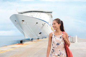 Wall Mural - Cruise Ship Vacation Happy Female Tourist on Pier. Smiling happy young woman walking on pier by huge cruise ship moored at jetty. Beautiful woman in casuals is enjoying her vacation.