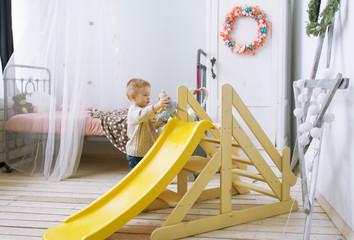 The kid plays in a nursery.
