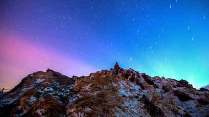 Star trails over the winter mountains landscape.