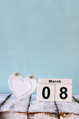 image of wooden March 8 calendar, next to white heart on old rustic table. selective focus