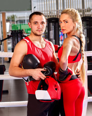 Female boxer with your male coach after workout in gym posing on camera.