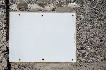 The white plastic board for posters on the stone wall.