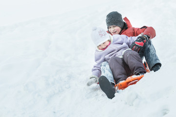 Sibling brother and little sister enjoying fast ride down snowy hill on orange snow slider
