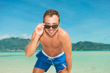 man on the beach posing in briefs while fixing sunglasses