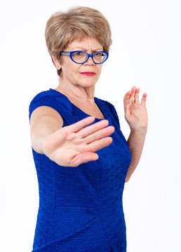 Worried Caucasian elderly woman saying no with and gesturing with arm out, white background