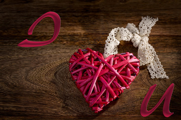red wooden heart with lace bow on wood and i love you written