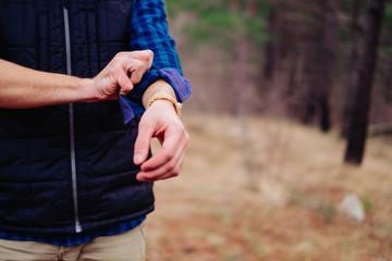 Hiker man rolling his sleeves