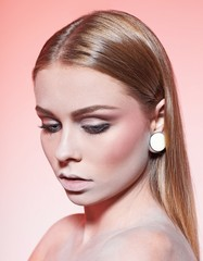 pink background. beautiful makeup. looking down