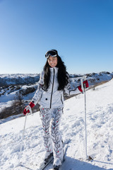 Pretty young female skier in a white ensemble