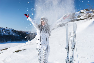 Laughing skier throwing snow on herself