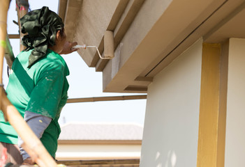 Painter on wooden scaffold painting  Exterior House