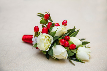 Beautiful wedding boutonniere of varios flowers on white wooden
