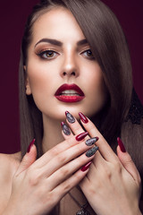 Pretty girl with unusual hairstyle, bright makeup, red lips and manicure design. Beauty face. Art nails.
