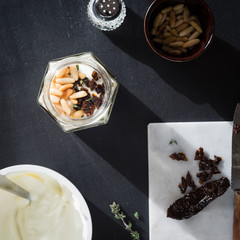 Greek yogurt with roasted pine nuts,  marinated dried tomatoes and thyme in jar on black background