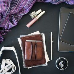 Accessories of young woman: phone, tablet, earphones, notebooks, pass, wallet, smartwatch, external battery, nail polish and lip gloss