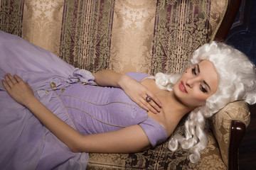 Woman in historic baroque style dress and white wig  on the couc