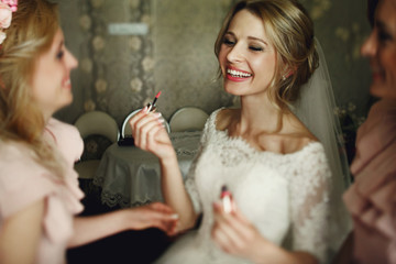 Beautiful blonde wedding bride and bridesmaids laughing in luxur