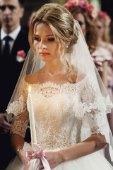 Beautiful emotional blonde bride holding candle in church in whi