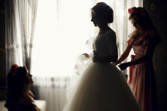 Bridesmaids in pink preparing beautiful elegant white dress brid