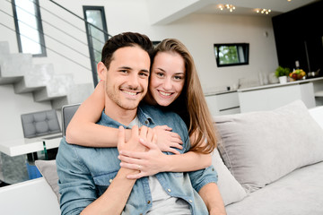portrait of happy young couple together at home in sofa