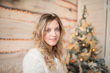 girl near the decorated Christmas tree in beautiful light interior