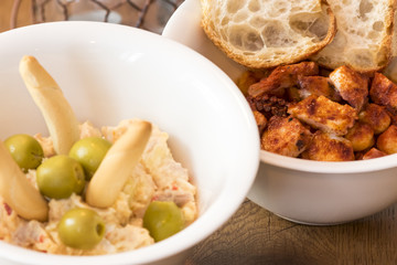 Ceramic bowls with Russian salad and  chickpeas and octopus