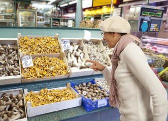 Woman buys raw mushroom in market
