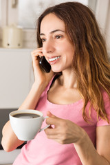 Woman with a cup of coffee talking the phone