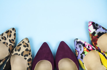 Stiletto shoes in different colours and patterns in a curved line on light blue background.