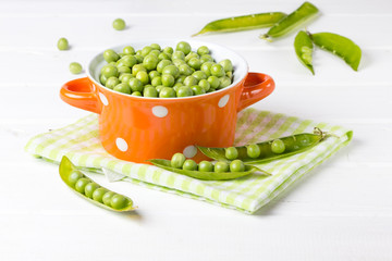 Fresh green peas in orange bowl on wooden white background