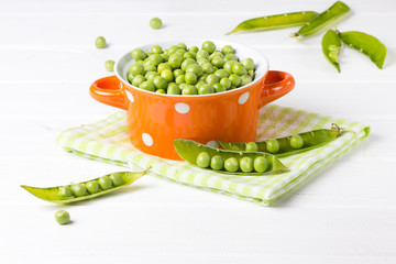 Bowl of fresh green peas on wooden white background