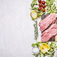 Two pork steak with vegetables on a cutting board with spices and herbs  border ,place for text on wooden rustic background top view close up