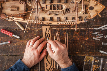 Man collects the vehicle model on the wooden table Wall mural