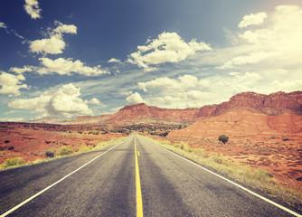 Vintage toned scenic desert road, USA.