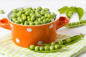 Fresh green peas in orange bowl on wooden white background