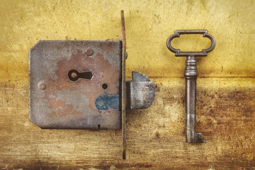 Ancient door lock with key on a metal background
