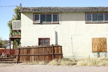 Heruntergekommenes Wohnhaus / Ein heruntergekommenes Wohnhaus am Rand einer Stadt mit Brettern vor den Fenstern und eingestürzten Zäunen.