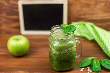 Healthy green smoothie with spinach, green apple and pine nuts in a jar mug on rustic wooden background from top view.