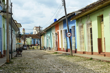Typical street in Trinidad (Cuba), with coloured houses and Saint Francis church as a background.