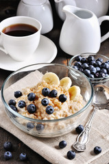 Oatmeal or porridge with blueberries, bananas, and brown sugar. Healthy breakfast. Toned image, selective focus