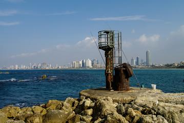 Fishing from pier in old Jaffa port. Panaramic view ti Tel Aviv.
