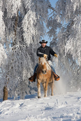 Man on horse riding through snowy landscape