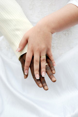 Black groom and white fiance hands with rings
