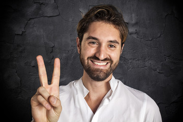 Smiling man showing victory gesture