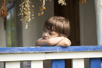 sad little boy on the porch of rural house