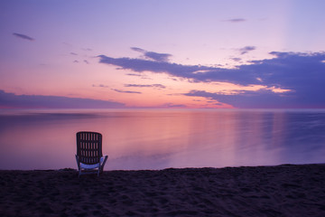 Wall Mural - one chair standing on the beach at sunset