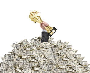 hand of a man stuck in a pile of money holding a trophy above th