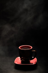 A cup of coffee with smoke on black background. Toned