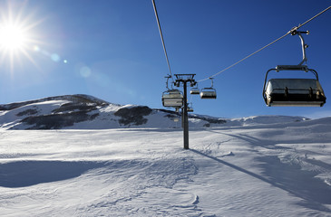Chair-lift and blue sky with sun